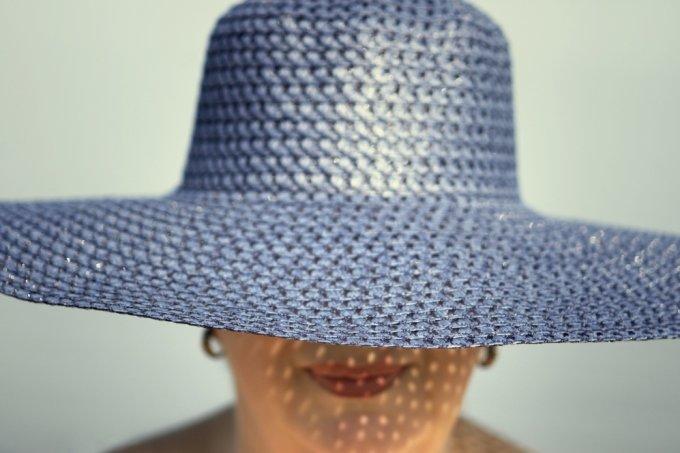 Mulher com chapéu sob o sol