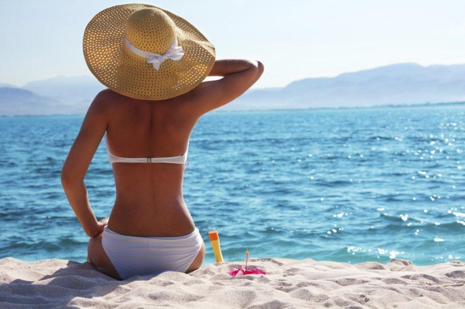 Mulher tomando sol com chapéu
