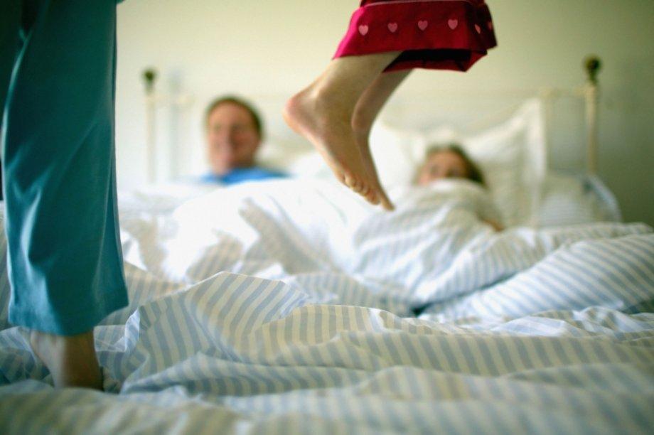 Crianças pulando na cama dos pais