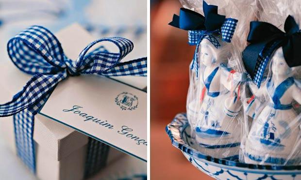 Caixinha branca com fita azul marcadora de lugar e bonequinhas de porcelana como minibalas de ovos de lembrancinha