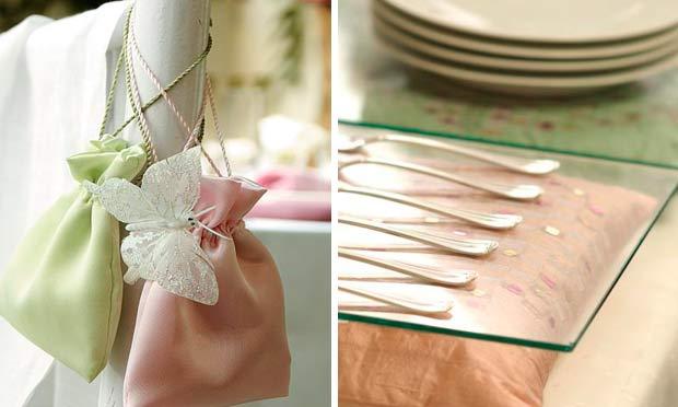 Talheres apoiados sobre almofada rosa e placa de vidro e saquinhos como lembrancinhas em verde e rosa