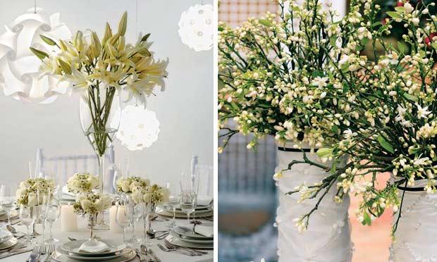 Mesa decorada em tons de branco com lustres redondos e flor de laranjeira