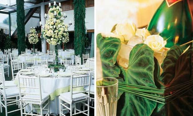 Arranjo de flores brancos suspenso e vaso de vidro enrolado em folhas com garrafas