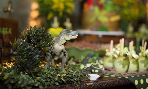 Dinossauro de brinquedo na mesa de doçes.
