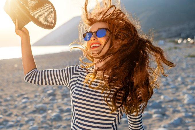 jovem-mulher-com-cabelos-ruivos-ao-vento-na-praia