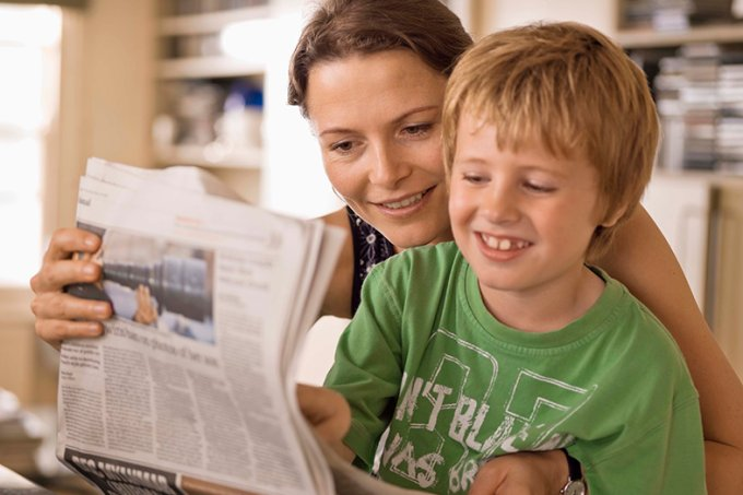 mãe lendo jornal com o filho