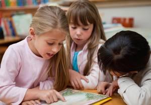 crianças lendo livro na escola