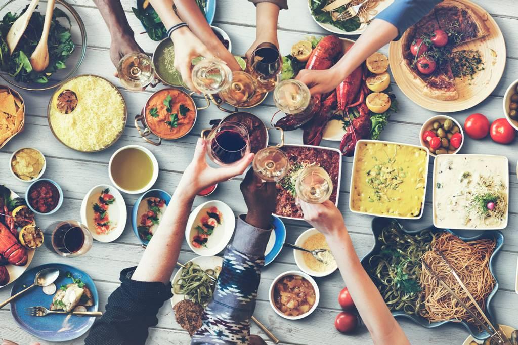 amigos-brindando-com-mesa-cheia-de-comida