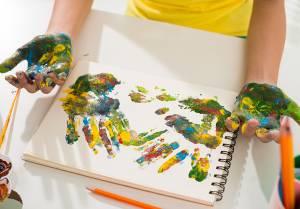criança pintando as mãos e o papel com tintas coloridas