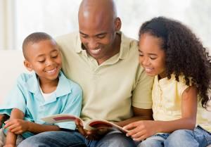 Pai lendo para filhos no sofá