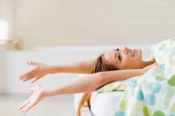 Smiling young woman lying in bed and stretching arms