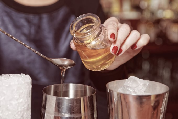 Bartender is adding honey to the glass, toned