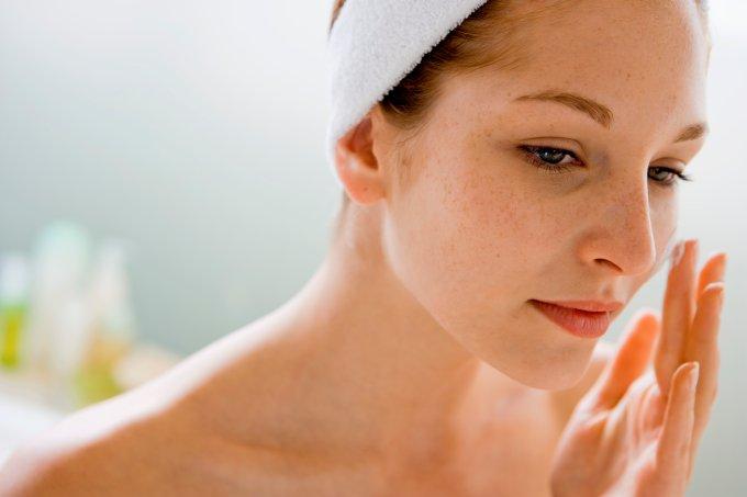 Woman using moisturizing cream