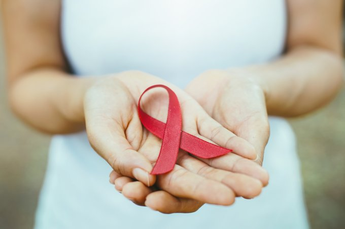 red aids ribbon in hand.