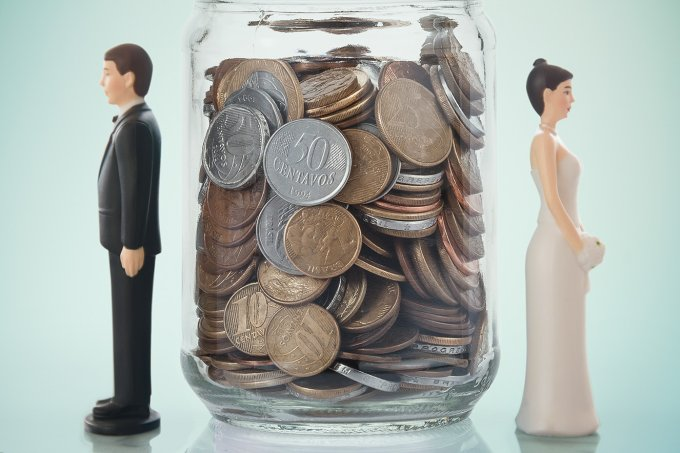 Close up of bride and groom dolls near savings jar