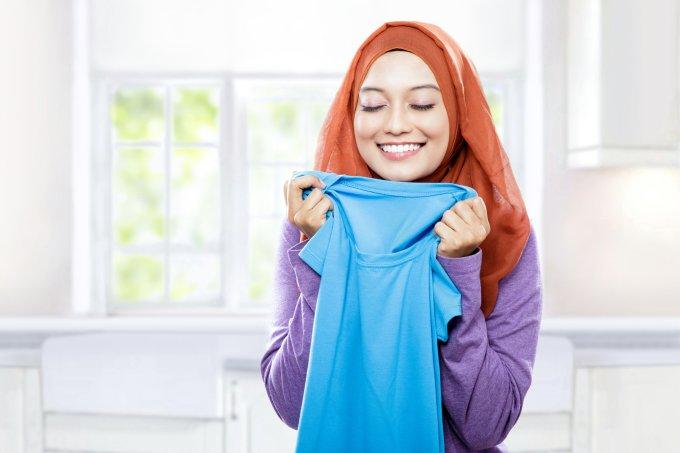 mulher cheirando roupa
