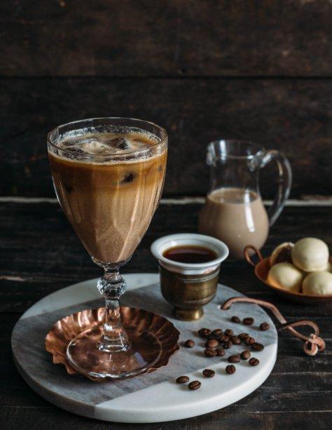 """<p style=""""text-align:justify;""""><b>Marula Mocha</b></p><p style=""""text-align:justify;"""">O café chega à happy hour em uma combinação de sabores muito similar ao nosso adorado café com leite.</p><p style=""""text-align:justify;"""">Ingredientes:</p><p style=""""text-align:justify;"""">100 ml de licor de marula</p><p style=""""text-align:justify;"""">80 ml de café espresso ou 120 ml de café coado</p><p style=""""text-align:justify;"""">2 bombons de chocolate branco recheados com wafer de avelã</p><p style=""""text-align:justify;"""">Gelo de café (Faça o café de sua preferência. Deposite nas forminhas de gelo e leve ao congelador.)</p><p style=""""text-align:justify;"""">Modo de preparo:</p><p style=""""text-align:justify;"""">Esfrie a taça previamente, colocando um pouco de água gelada no recipiente ou deixando-o um período na geladeira. Deposite o café e o gelo de café na taça gelada. No liquidificador, bata os bombons junto com o licor de marula. Em seguida, deposite a mistura na taça; o resultado é uma bebida bifásica.</p>"""