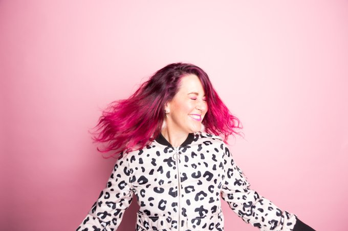 A woman with pink hair dances in front of a pink background