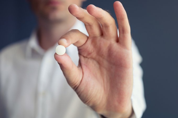Midsection Of Man Holding Pill