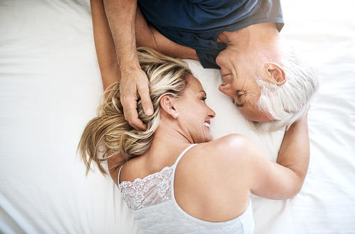 Shot of an affectionate mature couple lying in bed together at home