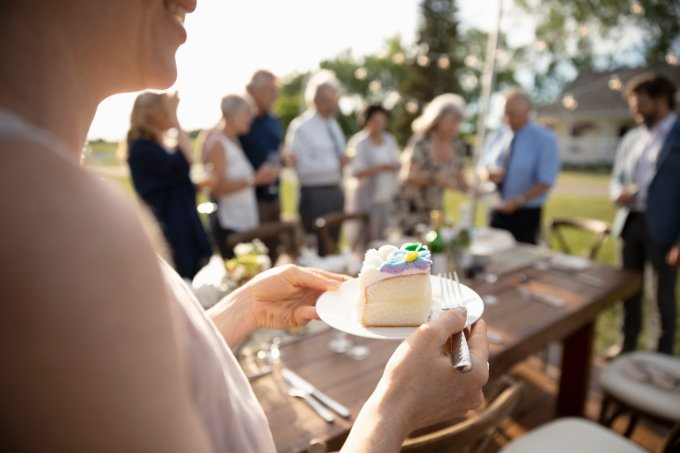 Woman eating cake, celebrating at sunny garden party with friends