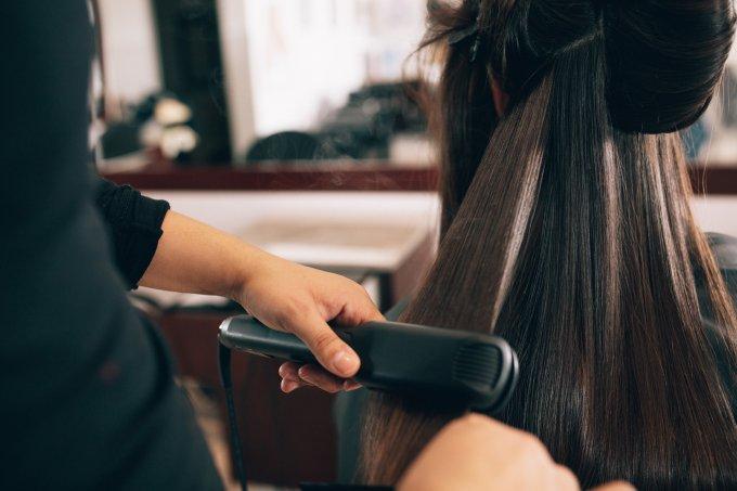 Cabeleireira fazendo chapinha em cabelo de cliente