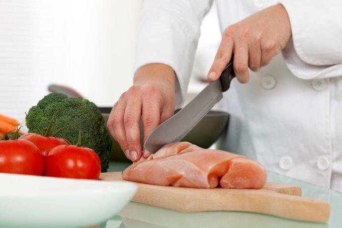 Pessoa cortando um pedaço cru de frango