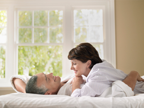 Side view of happy woman looking at husband while lying in bed