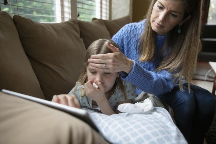 Mãe cuidando de criança com gripe