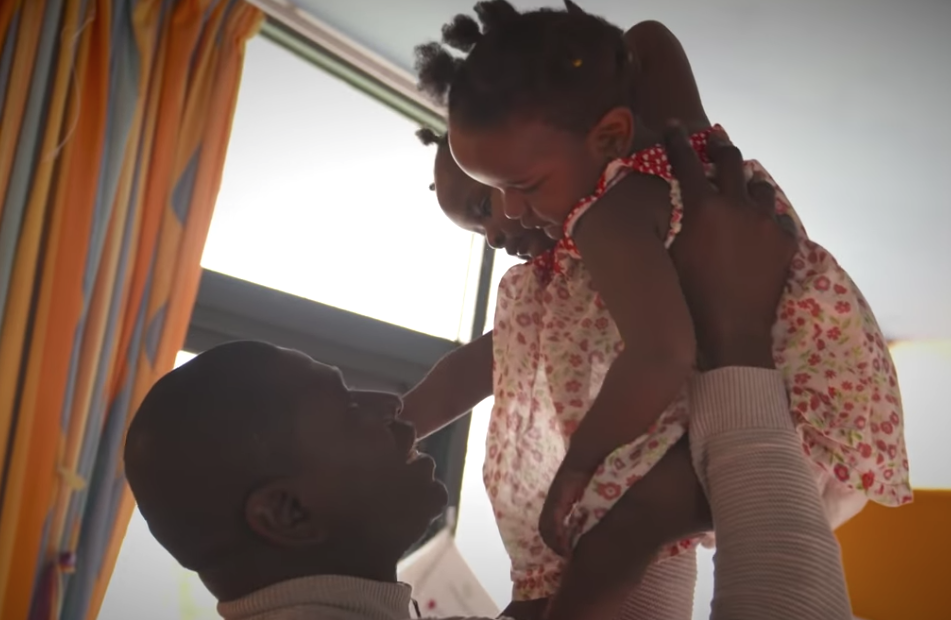 Ibrahima Ndiaye segurando suas filhas, gêmeas siamesas