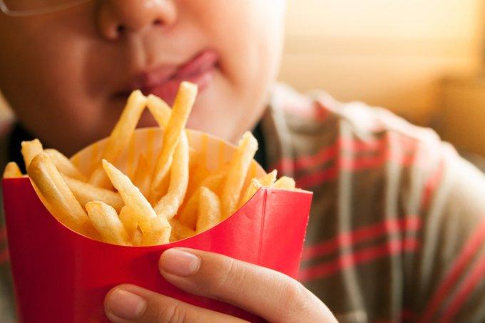 Criança comendo batata frita