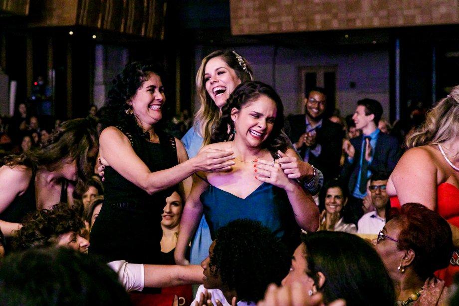 Luciana Carvalho (de preto) e Fernanda Abra, finalistas da categoria Inovação e Ciência, celebrando o anúncio da vencedora, a cientista Juliana Estradioto
