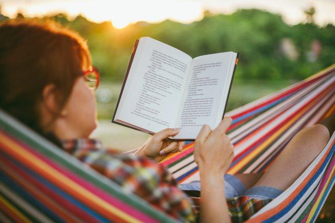 Mulher lendo livro deitada na rede