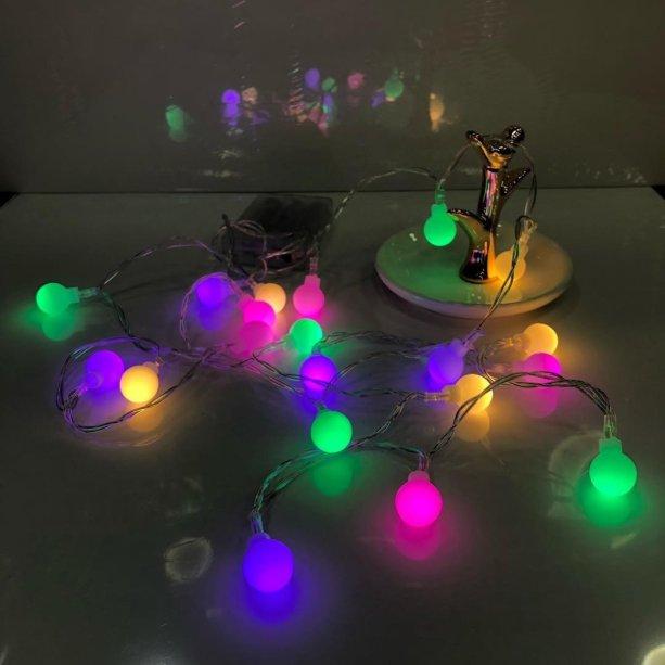 """Cordão de luzes coloridas, com 2 m, 20 lâmpadas bolinhas de LED, funciona com 3 pilhas AAA.<a href=""""https://www.elo7.com.br/2-luminaria-cordao-luz-led-20-bolinhas-1-5cm-varal-2m-color/dp/F5976E?pp=11&pn=1&nav=sts_ps_sr_1_11&qrid=NZqQJWSPOiEf#dmcl=1&rcp=1&hpa=0&ps2=1&sdps=0&rch=1&hsv=1&pcpe=1&ucrq=1&npc=1&supc=1&carf=0&droam=0&df=d&rps=0&srm=1&vpl=1&fsfv=0&sew=0&sami=1&sms=0&spc=1&staa=0&smsm=0&usb=0&ses=0&rcpd=1&sei=0&disc=0&suf=0&sura=0&smps=0&rfn=0&sedk=1&scsa=1&sewb=1&uso=m&smc=1&idfs=1&sum=0&sep=0&cpr=0&fnc=0&secpl=1&doar=0&inp=0&sed=1"""" target=""""_blank"""" rel=""""noopener""""> Elo 7 (Loja do Guru_Rio)</a>, R$ 59,98"""