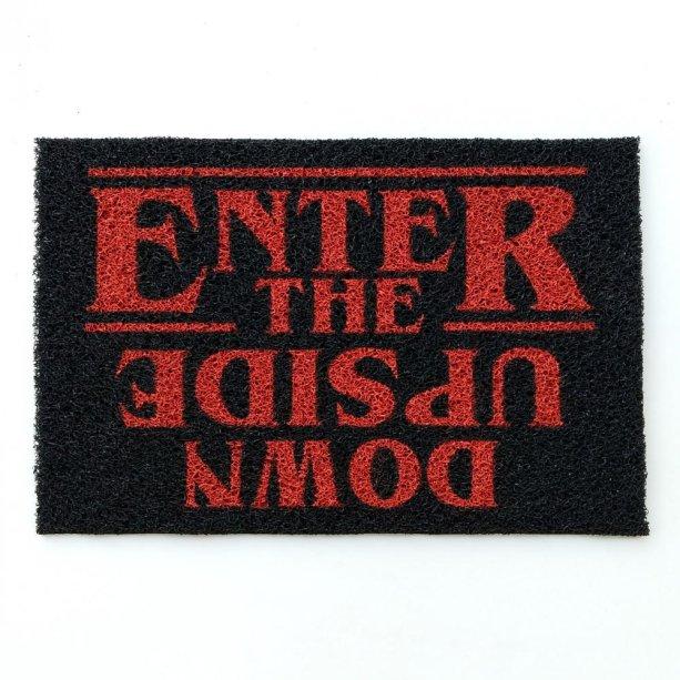 """Capacho Enter The Upside Down, 100% vinílico, 60 x 40 cm. <a href=""""https://www.artcutlab.com.br/capacho-stranger-things-enter-the-upside-down"""" target=""""_blank"""" rel=""""noopener"""">Art Cut Lab</a>, R$ 109,90"""