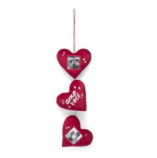 """Móbile de coração de poliéster, com espaço para duas fotos de 8 x 8 cm, na altura de 92 cm. <a href=""""https://www.ludi.com.br/mobile-porta-retrato-amor-e-tudo/p?event-category=beon&event-action=details&event-label=product_related_category"""">Ludi</a>, R$ 99,90"""