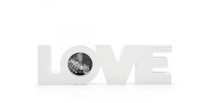 """Porta-retrato Love, de plástico, nas medidas 29,5 x 9 cm, com espaço para uma foto de 6,5 x 6,5 cm. <a href=""""https://www.ludi.com.br/porta-retrato-love/p"""">Ludi</a>, R$ 36,90"""
