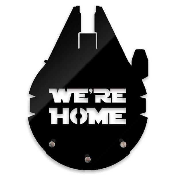 """Porta-chave We´re Home, de acrílico com três ganchos em metal, de 12x 16 cm. <a href=""""https://nerdstore.com.br/produto/porta-chaves-were-home/"""" target=""""_blank"""" rel=""""noopener"""">Nerd Store</a>, R$ 34,90"""