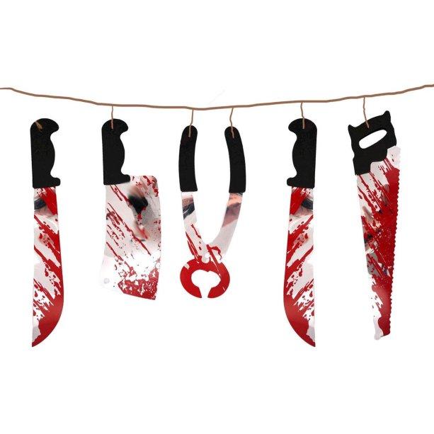 """Varal de facas com sangue, de laminado e EVA, com 2 m de extensão. <a href=""""https://www.maxfesta.com.br/varal-de-facas-com-sangue-24237/p?cc=236"""" target=""""_blank"""" rel=""""noopener"""">Max Festa</a>, R$ 10,90"""