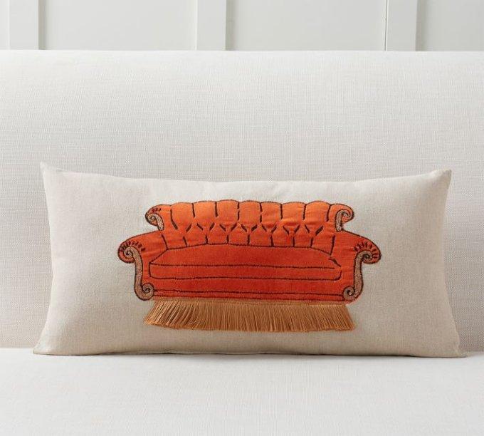 "<a href=""https://www.potterybarn.com/products/friends-central-perk-sofa-pillow/?pkey=cfriends-tv-pottery-barn&isx=0.0"">Almofada</a> nas medidas 30 x 60 cm, de algodão, no valor US$ 45,50"