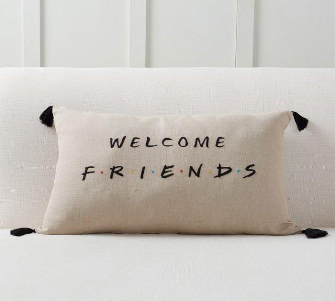 """<a href=""""https://www.potterybarn.com/products/friends-welcome-pillow/?pkey=cfriends-tv-pottery-barn&isx=0.0"""">Almofada</a> nas medidas 40 x 66 cm, de algodão e linho, no valor US$ 49,50"""