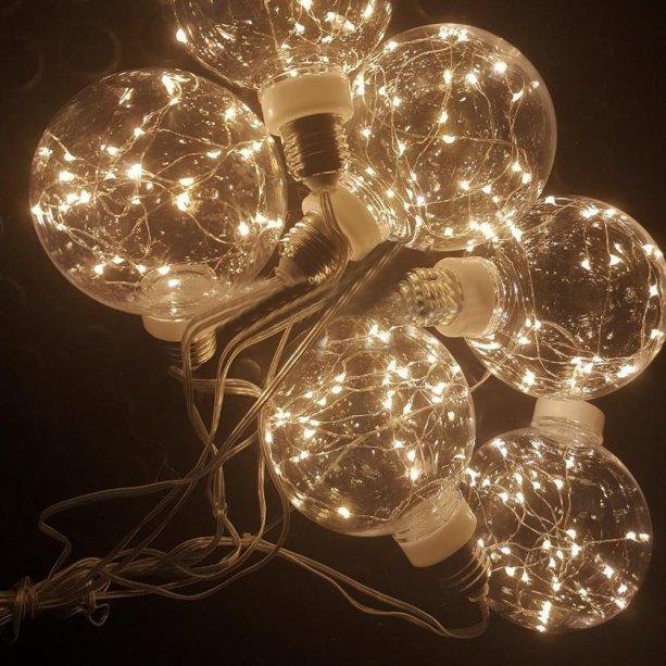 """Cordão de Luz com lâmpadas LED com fio de fada, de 1,70 m, com plugue bivolt (3W). <a href=""""https://www.shoptime.com.br/produto/55436445/cordao-de-luz-com-6-lampadas-led-fio-de-fada-bola-g95-3000k"""" target=""""_blank"""" rel=""""noopener"""">Shoptime</a>, R$ 119,99"""