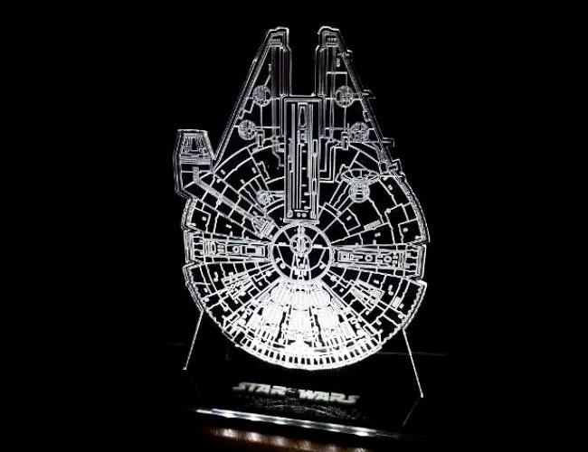 "Luminária de acrílico Millenium Falcom, de LED, com 17 cm de altura (110 ou 220 V). <a href=""https://www.artgeek.com.br/luminarias/luminaria-acrilico-star-wars-millenium-falcom/1724?gclid=EAIaIQobChMI8q3DyaSC4gIVjAuRCh3oswifEAkYHyABEgIPHfD_BwE"" target=""_blank"" rel=""noopener"">Artgeek</a>, R$ 110,90"