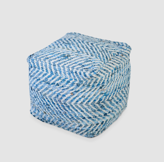 """O puff de tecido azul e branco custa R$ 1.035 na <a href=""""https://www.collector55.com.br/puff-tecido-azul-e-branco/p"""">Collector 55</a>."""