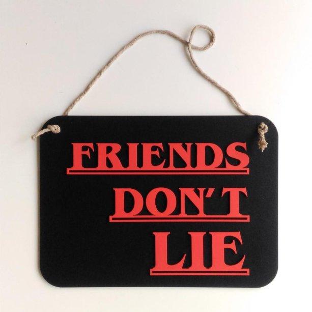 "Placa Friends Don´t Lie, de MDF, 29 x 21 cm. <a href=""https://www.artcutlab.com.br/friends-dont-lie"" target=""_blank"" rel=""noopener"">Art Cut Lab</a>, R$ 44,90"