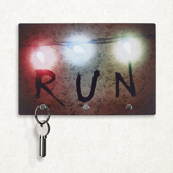 "Porta-chave Run, de plástico com ganchos metálicos, 23 x 15,5 cm. <a href=""https://www.f2fstore.com.br/Porta-Chaves-Stranger-Things-Run"" target=""_blank"" rel=""noopener"">F2F Store</a>, R$ 34,90"