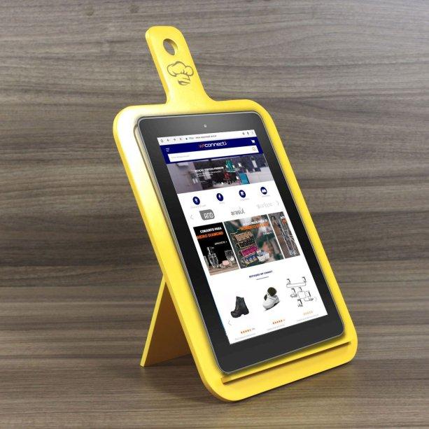 """Suporte para tablet no formato de tábua de carne, de MDF, medidas de 23 x 40 cm. <a href=""""https://www.magazineluiza.com.br/suporte-para-livro-de-receitas-tablets-em-mdf-decoracao-cozinha-geton-concept/p/kd75d36525/tb/sket/"""" target=""""_blank"""" rel=""""noopener"""">Magazine Luiza</a>, R$ 79,90"""