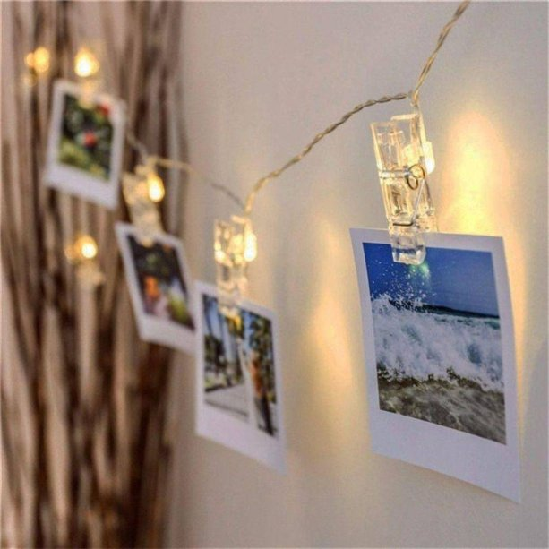 """Varal de fotos com 10 pregadores com LED, com duas pilhas AA (não inclusas). <a href=""""https://www.zonacriativa.com.br/luminaria-varal-de-fotos--10081896/p"""" target=""""_blank"""" rel=""""noopener"""">Zona Criativa</a>, R$ 49,90"""