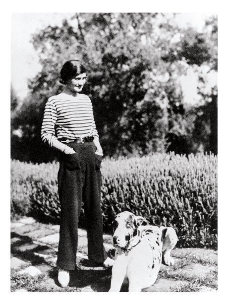 Coco Chanel, de camisa listrada e calça comprida, duas de suas criações para as mulheres.