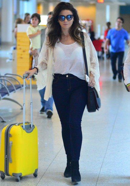Aqui, ela escolheu jeans skinny, top branco básico e quimono com rendas e transparências para viajar de avião.